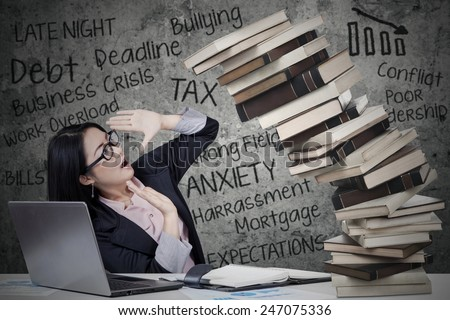 Stressed businesswoman with collapse books and job problems - stock photo