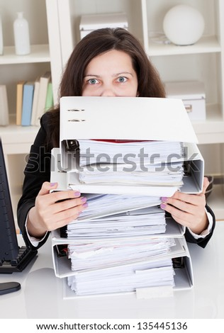 Stressed Businesswoman Working In Office With Stack Of Folders - stock photo