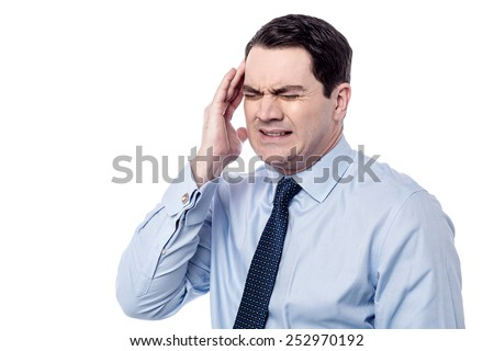 Stressed corporate man suffering from headache - stock photo