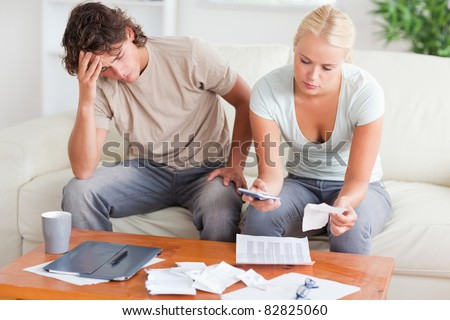 Stressed couple calculating their expenses in the living room - stock photo