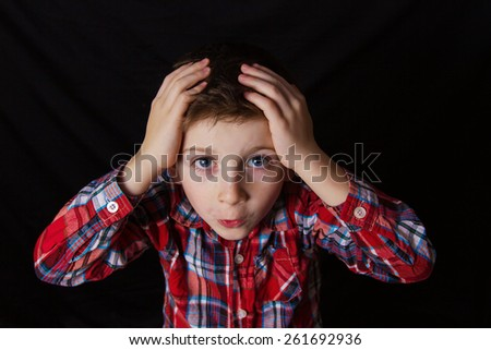 Stressed,depressed,unhappy little boy holding hands on her head over yellow background. - stock photo