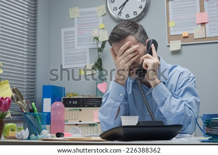 Stressed employee on the phone touching his forehead. - stock photo