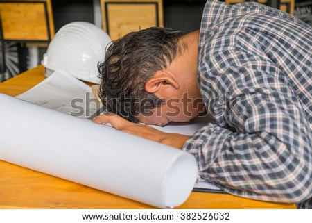 Stressed engineer  due to the of amount of work he has to do. - stock photo