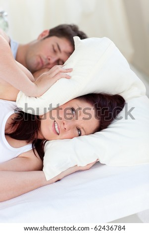 Stressed future mom with head under the pillow in bed with her husband snoring during the morning - stock photo