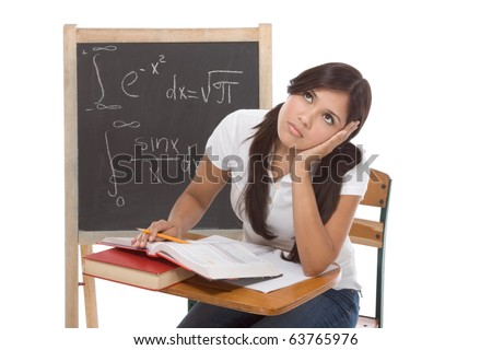 Stressed High school or college Latina female student sitting by the desk at math class. Blackboard with complicated advanced mathematical formals is visible in background - stock photo