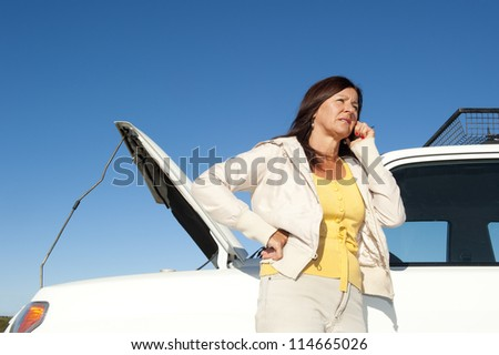 Stressed mature woman breakdown with car on remote road calling for service, assistance, for help on mobile phone, isolated with blue sky as background and copy space. - stock photo