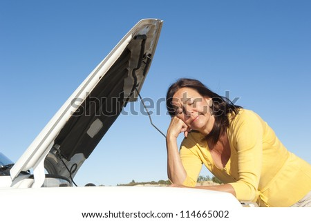 Stressed mature woman breakdown with car on remote road waiting for assistance, for help, isolated with blue sky as background and copy space. - stock photo
