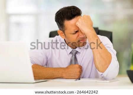 stressed middle aged businessman sitting in office - stock photo