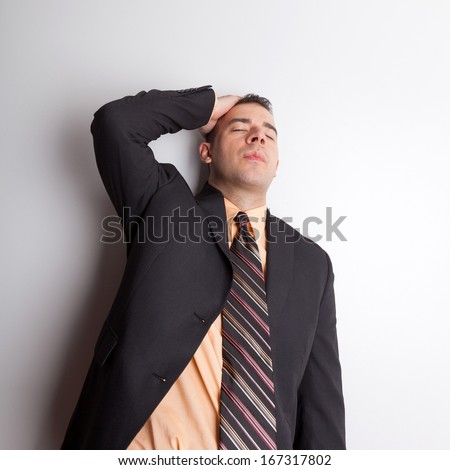 Stressed out business man isolated over a silver background worried or depressed about finances and difficult economic times. - stock photo