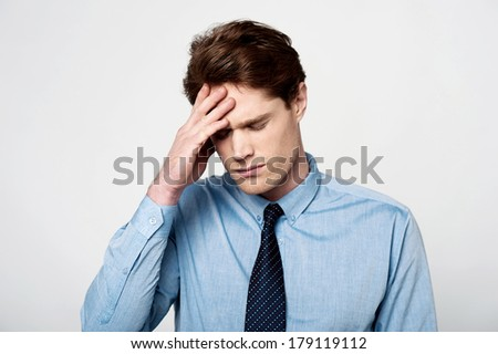 Stressed-out businessman with hand on his head - stock photo