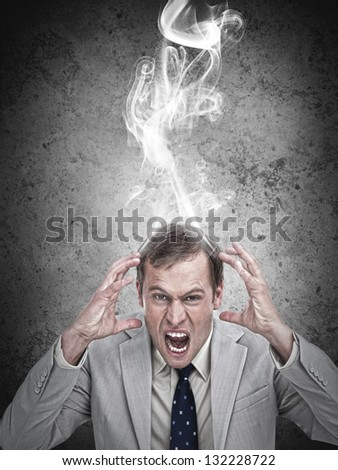 Stressed out hot headed businessman on grey background - stock photo