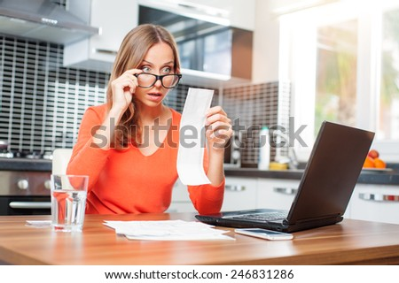 stressed over bills. Surprised young woman looking at her financial debts in the kitchen at home wearing orange pullover sitting at dining table. - stock photo