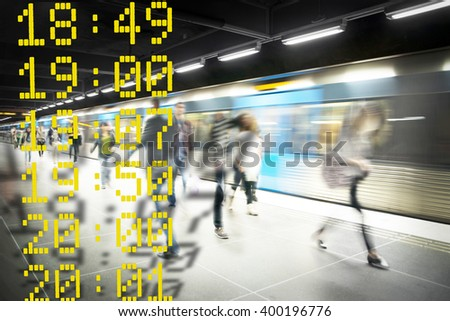 Stressed people on subway platform with moving blue train and departure times in foreground