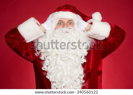 Stressed Santa. Saint Nicholas covering his ears with his hands in frustration - stock photo