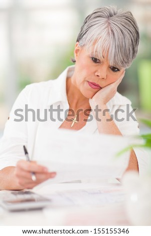 stressed senior woman paying her bills - stock photo