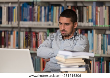 Stressed Student Of High School Sitting At The Library Desk - Shallow Depth Of Field - stock photo