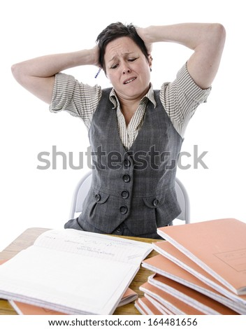 stressed teacher trying to mark a pile of students work - stock photo