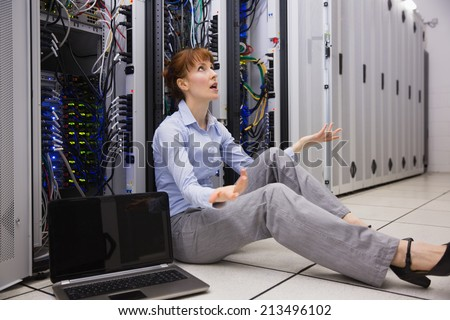 Stressed technician sitting on floor beside open server in large data center - stock photo