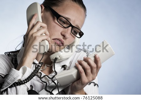 Stressed unhappy telephonist in call center wrapped with phone cables being over-strained with work, isolated on blue background. - stock photo