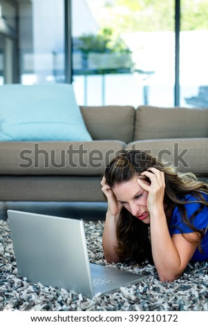 stressed woman, lying on the ground, looking at her computer with her head in her hands