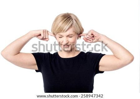Stressed woman plugging ears with fingers - stock photo