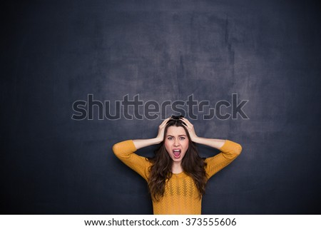 Stressed woman screaming over black background - stock photo