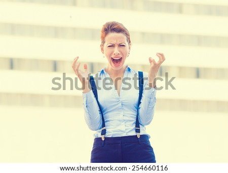 Stressed worried young woman corporate employee having headache screaming in frustration isolated outdoors corporate office window building background. Negative human emotion face expression   - stock photo