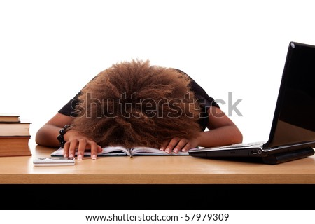 Stressed young black woman,  sitting at a table among books and laptop on a white background.