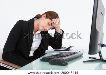 Stressed young businesswoman leaning at computer desk in office