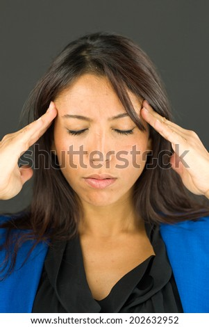 Stressed young businesswoman suffering from headache - stock photo