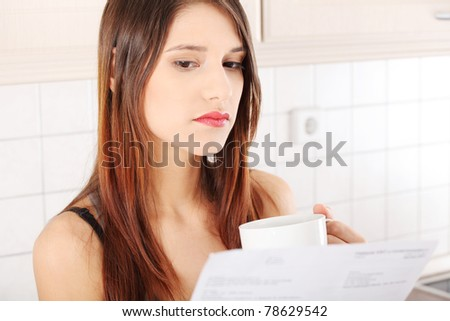 Stressed young caucasian woman in the kitchen drinking something hot and reading bill - stock photo