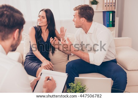 stressed young family quarrel at a reception at the psychologist - stock photo