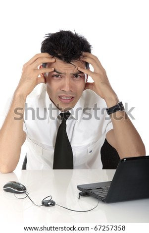 Stressed young Nepalese businessman in office at desk in front of a laptop holding his head. Studio shot. White background - stock photo