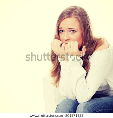 Stressed young woman eating her nails. - stock photo