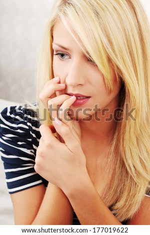 Stressed young woman eating her nails  at home - stock photo