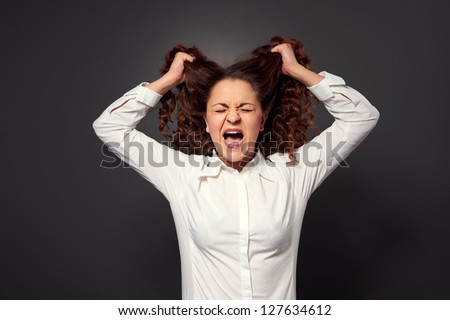 stressed young woman over grey background - stock photo