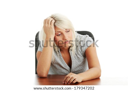 Stressed young woman sitting behind a desk, isolated on white