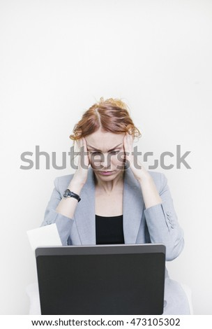 Stressful Business woman sitting in front of her laptop with hands on head