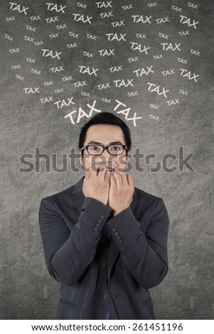 Stressful businessman biting his nail while thinking his tax, shot against gray background - stock photo