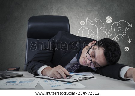 Stressful caucasian businessman closed eyes and sleeping on desk with paperwork - stock photo