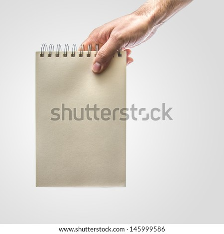 Stretched Hand holding a notebook - stock photo