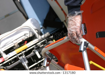 Stretcher bearer carring an invalid chair with background an ambulance litter. - stock photo