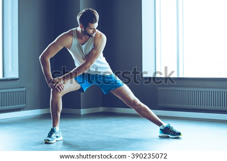 Stretching after great work out. Young handsome man in sportswear doing stretching at gym