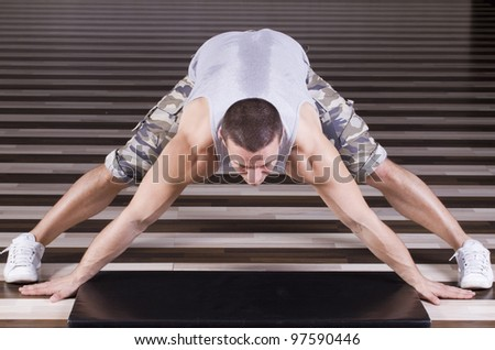 Stretching exercise after hard workout in the gym - stock photo