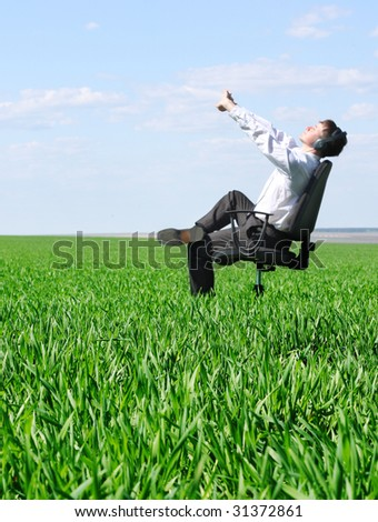 Stretching man on chair in green field - stock photo