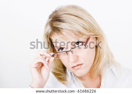 Strict blonde girl with glasses on a light background - stock photo