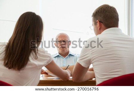 Strict boss sitting at the table and looking on his subjects - stock photo