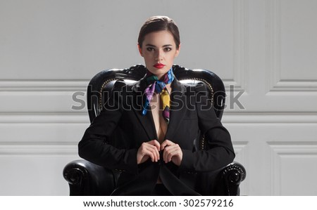 strict business woman in black suit sitting in chair - stock photo