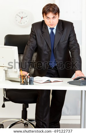 Strict modern business man standing at office desk