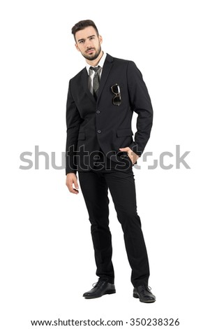 Strict rigid businessman looking at camera with sunglasses in suit pocket. Full body length portrait isolated over white studio background.